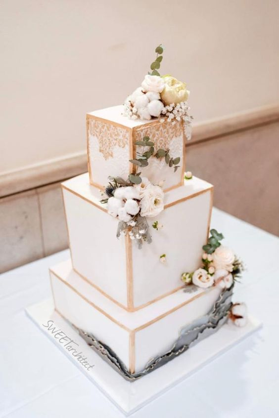 a luxurious white wedding cake with gold framing, fresh blooms and greenery