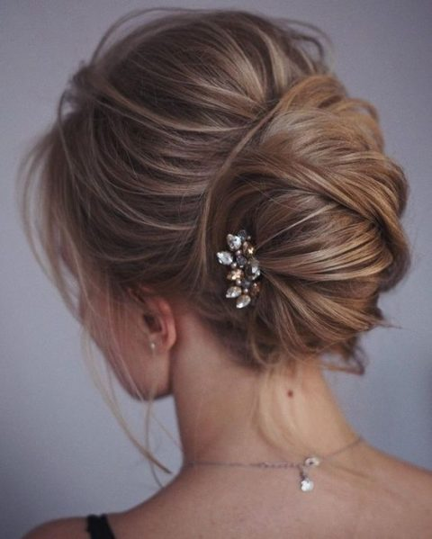 a messy twisted chignon with locks down and a small rhinestone hairpiece on one side