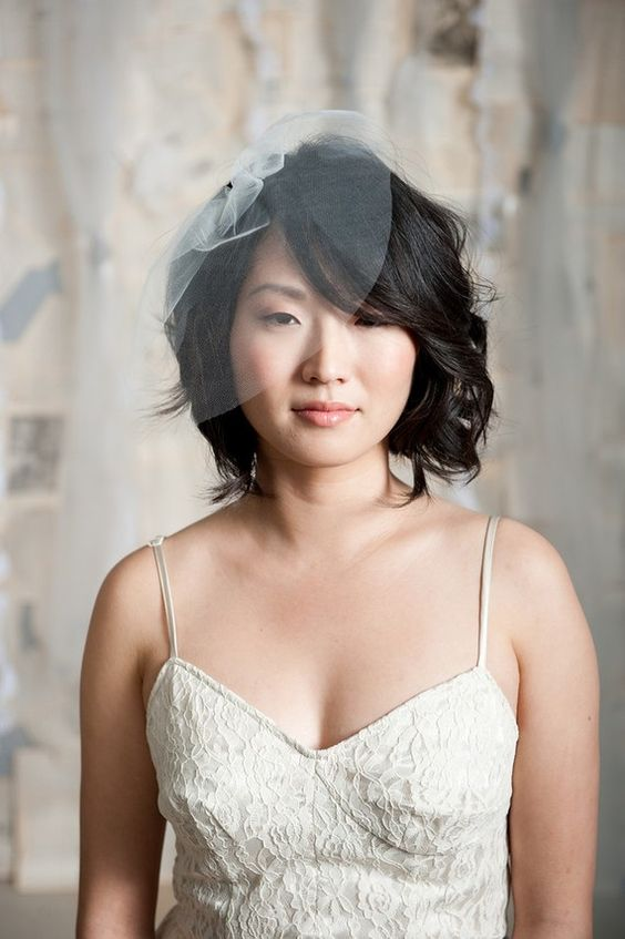 a mini sheer veil designed as a floral on one side of the head is a lovely and chic idea for a refined bride