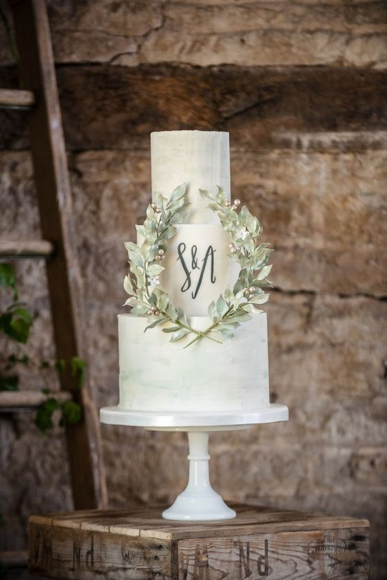 a modern green watercolor wedding cake with black monograms and sugar leaves plus beads is very cool and bold