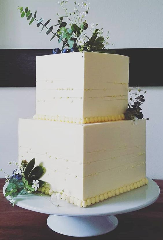 a modern rustic square wedding cake topped with wildflowers and eucalyptus