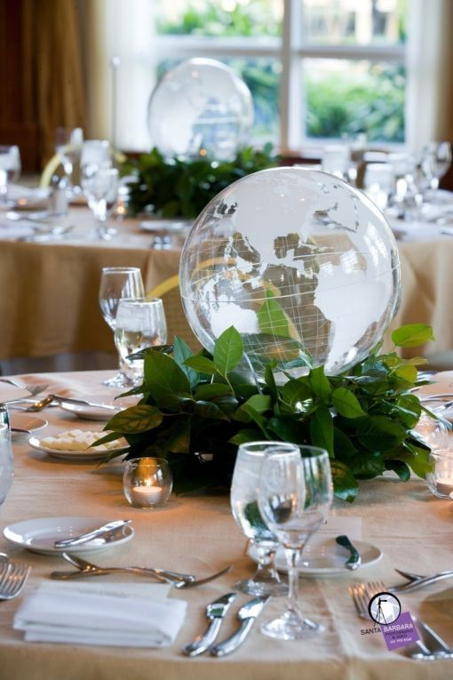 a modern wedding centerpiece of a greenery wreath and a sheer globe is a stylish idea for a travel-themed wedding