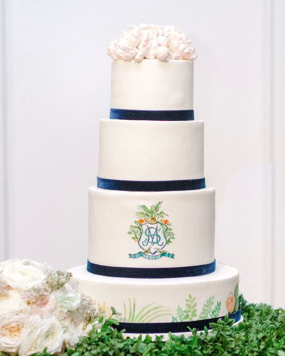a multi-tiered wedding cake with navy velvet ribbons, blooms and a painted ribbon plus a monogram and some blooms on top