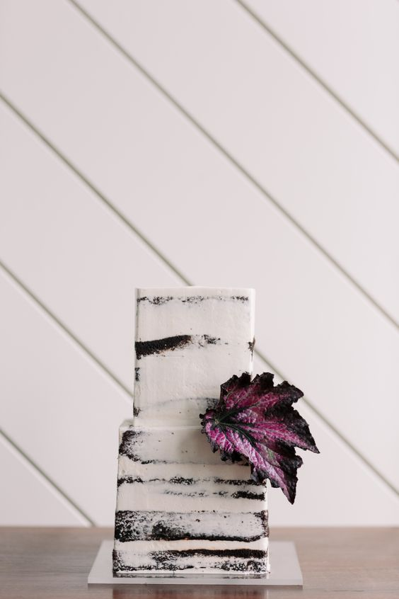 a naked chocolate square wedding cake with a single purple leaf for a moody fall wedding