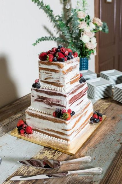 a naked wedding cake with fresh berries is a simple and cute idea for a summer wedding