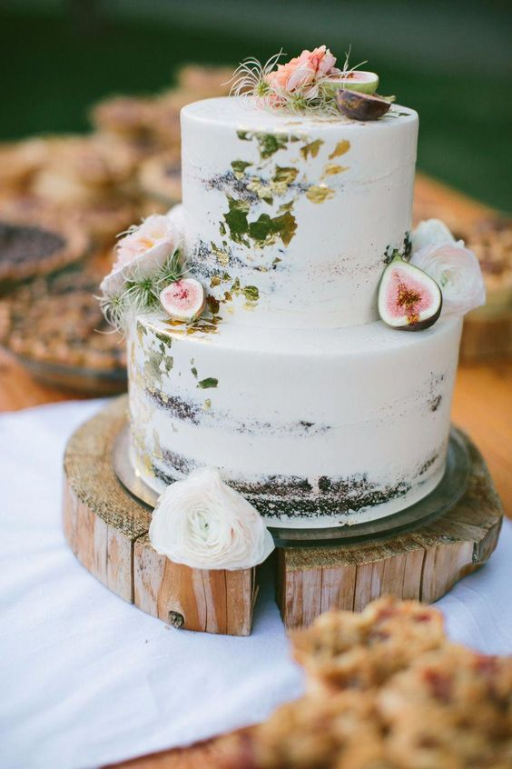 a naked wedding cake with gold leaf, figs, apples and pink blooms and air plants is a gorgeous idea