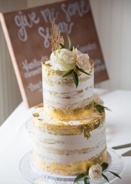 a naked wedding cake with gold leaf, neutral and pastel blooms and a gold cake topper
