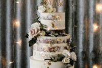 a naked wedding cake with gold leaf, white and blush blooms, leaves and a wooden calligraphy topper