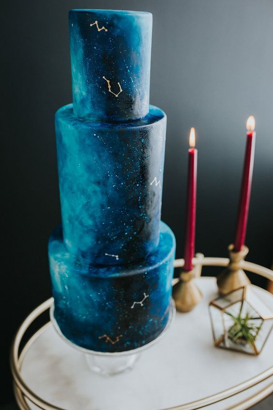 a navy and turquoise wedding cake with a watercolor effect and gold constellations for a celestial wedding