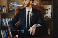 a navy suit, a black tie, a greenery boutonniere, striped socks for an accent and a man bun for a mid-century modern look