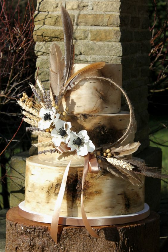 a neutral bark wedding cake with a wreath with sugar blooms, feathers, herbs and dried elements for a rustic wedding