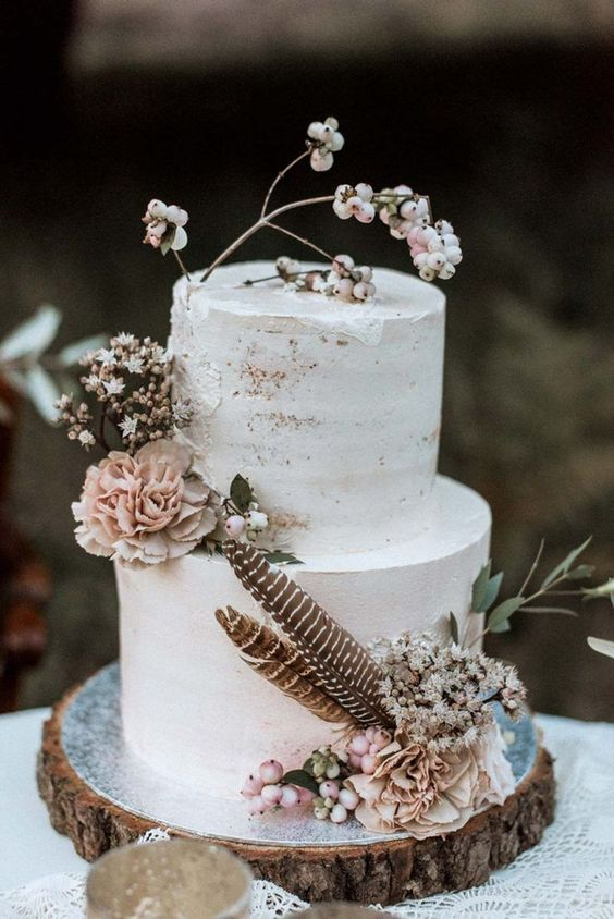 a neutral partly naked wedding cake with white blooms, berries, greenery and feathers for a boho or rustic wedding