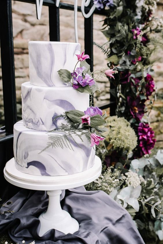 a non-typical purple marble wedding cake with purple and pink blooms and greenery for a purple or lilac wedding