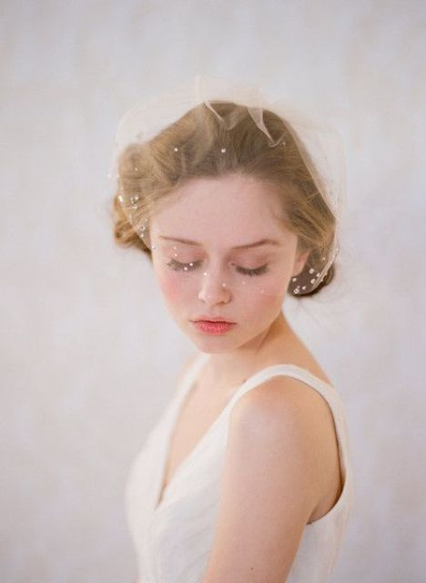 a nude mini veil with crystals on the edge is a very chic and beautiful idea that looks ethereal
