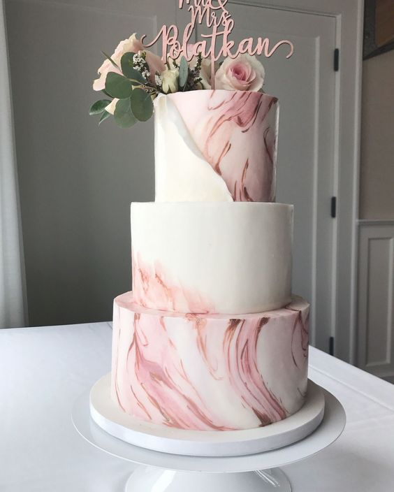 a pink marble wedding cake with a pink calligraphy, blush blooms and greenery is a beautiful and refined idea
