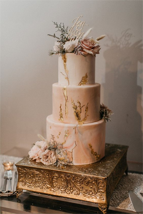 a pink marble wedding cake with gold leaf, frehs blush blooms and greenery and a calligraphy topper looks refined and very romantic at the same time