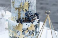 a quirky grey watercolor wedding cake with gold leaf and privet berries is cool for winter