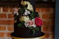 a refined black wedding cake with gold leaf, greenery and bold blooms is a stylish and very chic idea to try