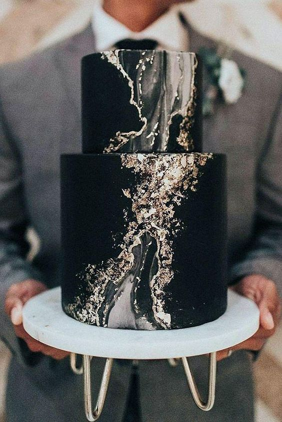 a refined black wedding cake with grey marble and gold leaf is a very beautiful and bold statement