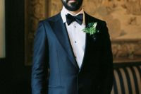 a refined groom's look with a black tux, a black bow tie, a greenery boutonniere, a full beard and a man bun