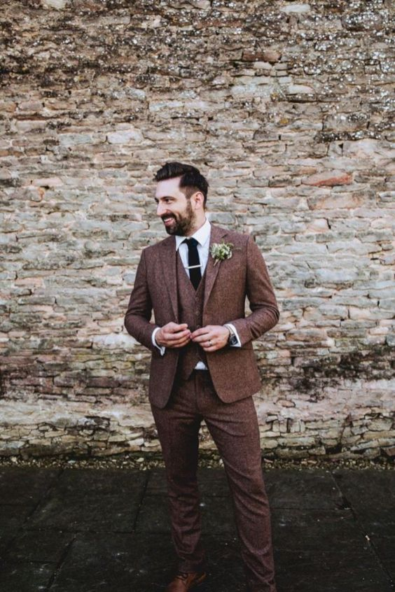 a refined groom's look with a three-piece rust tweed suit, a white button down, a blakc tie and brown shoes