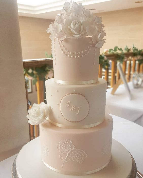 a refined wedding cake with white and blush tiers, with polka dots, floral patterns, pearls, white sugar roses is elegant