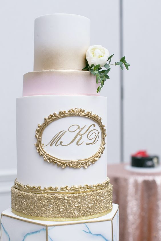a refined wedding cake with white, pink and gold tiers, gold frame and monograms is a great idea for a formal wedding