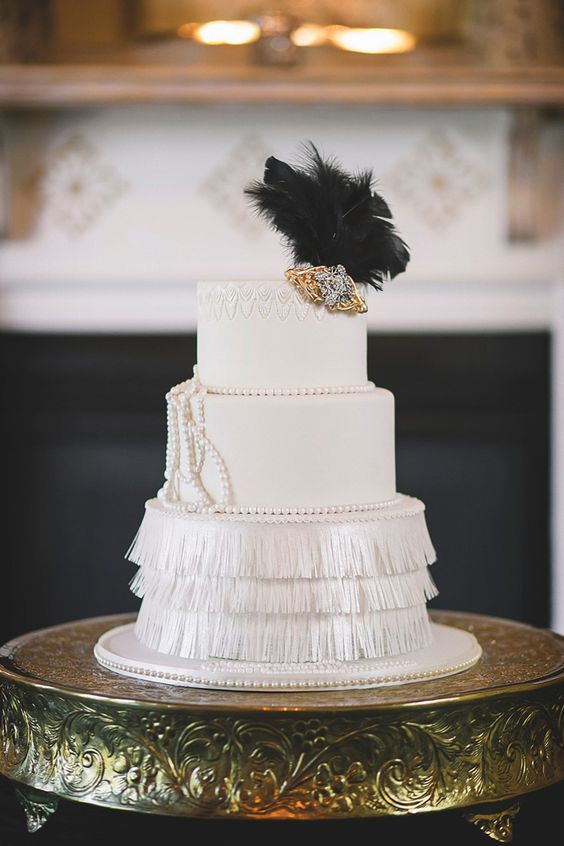 a refined white art deco wedding cake with a fringe tier and pearls, a large embellishment and black feathers