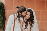 a relaxed boho look with a white shirt, rust suspenders, brown pants and a man bun plus some hair down for a more relaxed feel