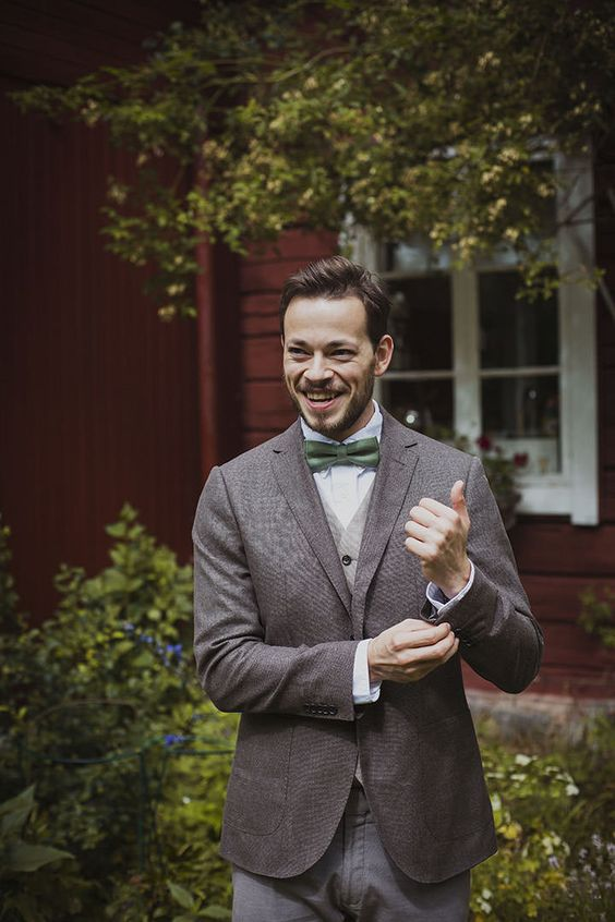a relaxed groom's outfit with a brown tweed blazer, grey pants, a grey waistcoat, a white button down and a green bow tie
