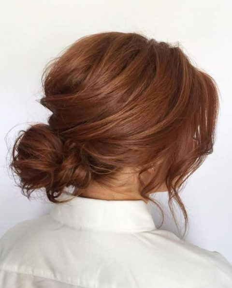 a relaxed messy low bun with a bump and some locks down for a casual bride
