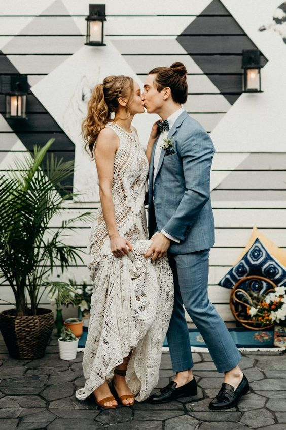 a relaxed summer boho groom look with a grey suit, a printed bow tie, black moccasins and a stylish man bun