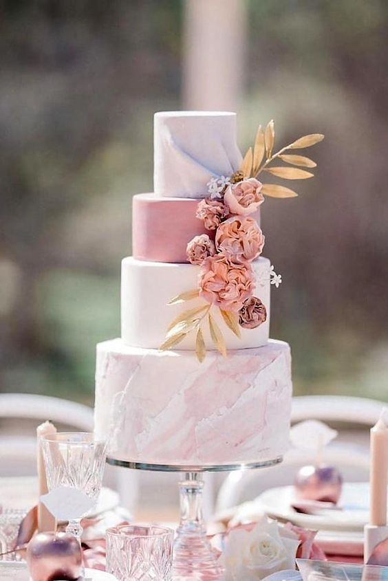 a romantic wedding cake with a white, pink and pink marble tier, dried blooms and gold foliage is a very romantic option