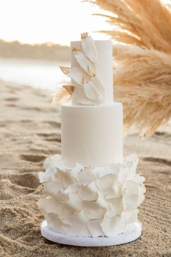 a romantic white wedding cake with sleek and ruffle tiers, with gold tipped feathers