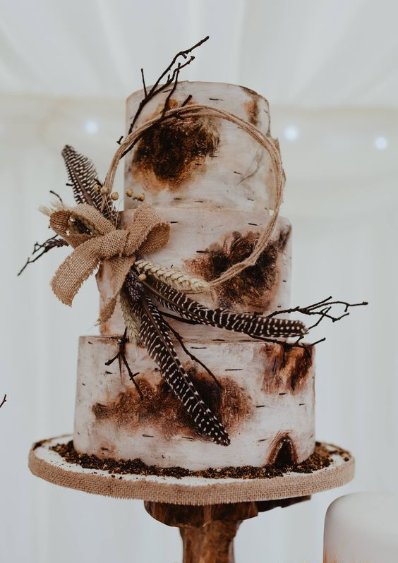 a rustic birch bark wedding cake with a wreath with feathers, a burlap bow and berries for a rustic or boho wedding