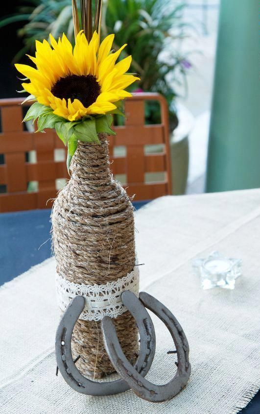 a rustic wedding centerpiece of a twine wrapped bottle with a sunflower and horseshoes