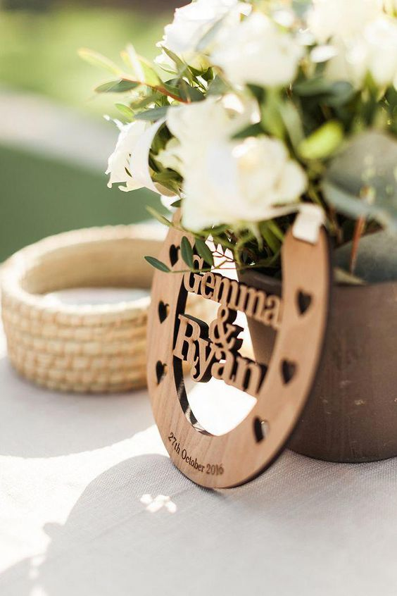 a rustic wedding centerpiece of a vase, white blooms and greenery and a plywood horseshoe with names