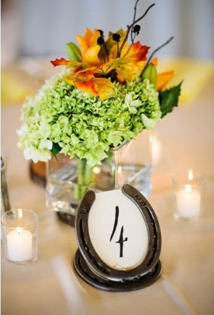 a rustic wedding centerpiece of green hydrangeads and bold leaves, candles and a horseshoe table number