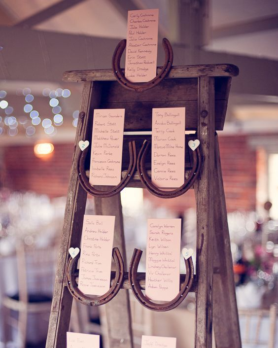 a rustic wedding seating chart of a vintage ladder, horseshoes and cards is a cute DIY idea