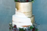 a semi naked wedding cake with much gold leaf, berries and thistles looks bold and catchy