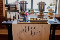 a simple and stylish coffee bar with silver tanks, a fabric sign and lots of sweets and coffee cups