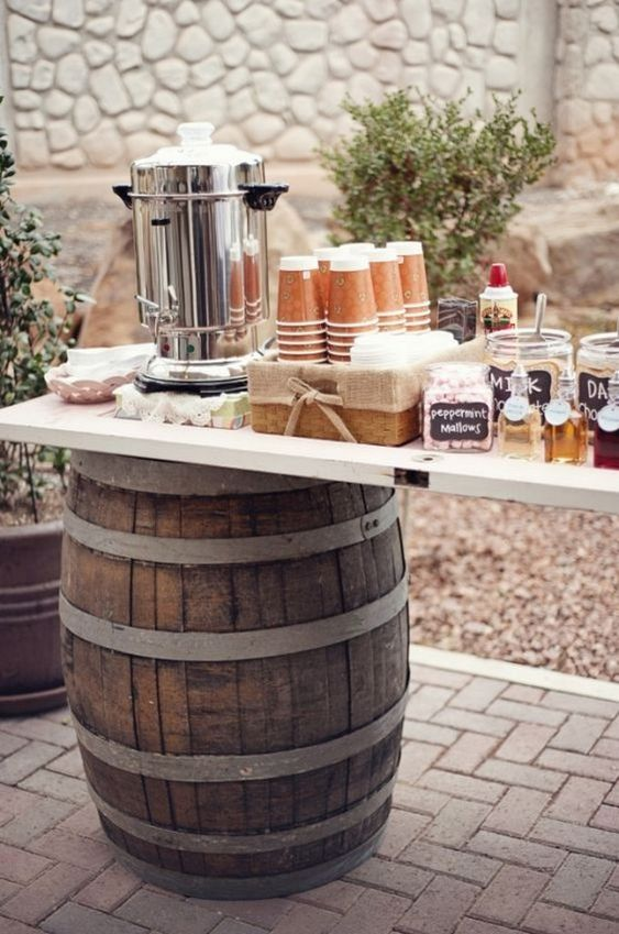 a simple rustic wedding coffee bar of two barrels and a tabletop plus lots of sweets, cups and syrups there