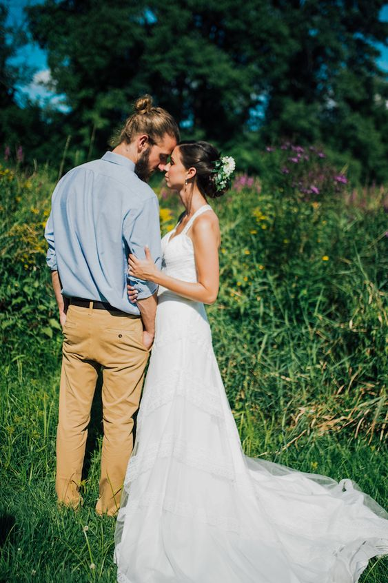 a simple summer boho groom look with a blue shirt, tan pants, a full beard and a man bun is relaxed and cool