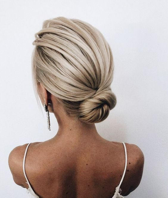 a sleek low bun with a bump is a cool idea is a great option for a minimalist or modern bride
