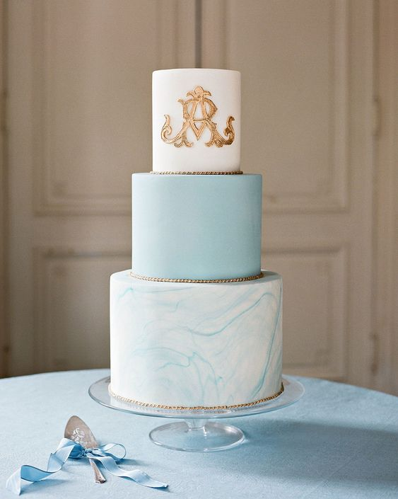 a sophisticated modern wedding cake with a blue, marble blue and white tiers, with gold touches and a pretty monogram