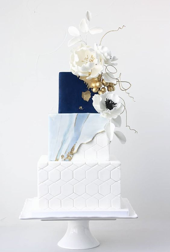 a sophisticated wedding cake with a white hex, watercolor blue and gold and navy tiers and sugar blooms and berries