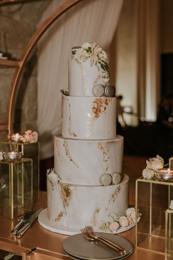 a sophisticated white marble wedding cake with gold leaf, macarons and white blooms is a gorgeous solution for many weddings