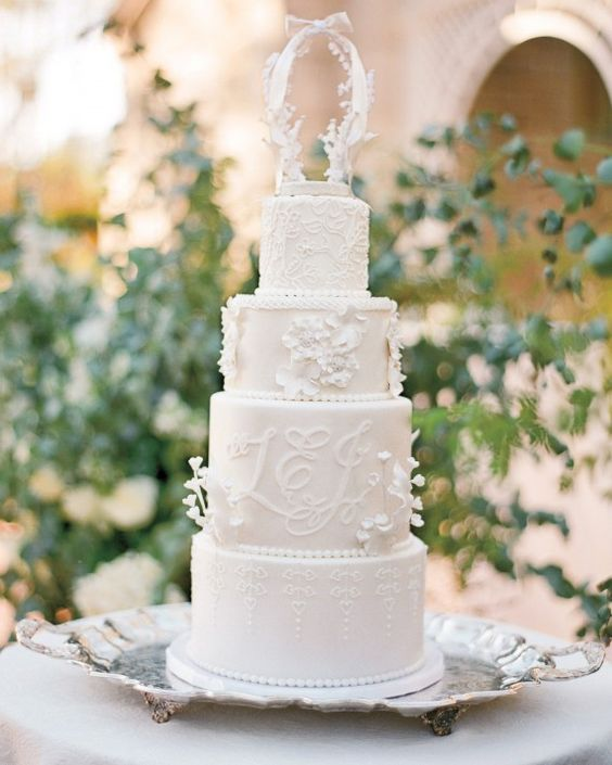 a sophisticated white wedding cake with floral and patterned tiers, with white sugar blooms and a sugar arch with a bow on top