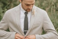 a spring or summer groom outfit with a neutral suit, a printed tie, a dried leaf boutonniere and a man bun on top