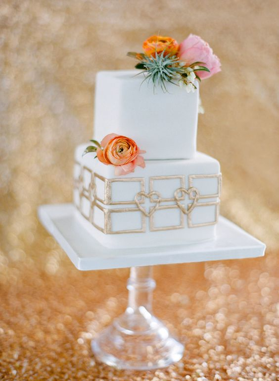 a square wedding cake with gold decor and fresh blooms and an air plant on top for an elegant wedding